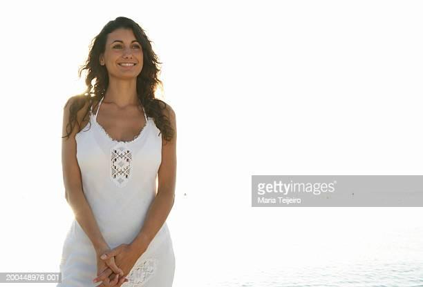 young woman wearing white dress standing on beach, smiling - weißes kleid stock-fotos und bilder