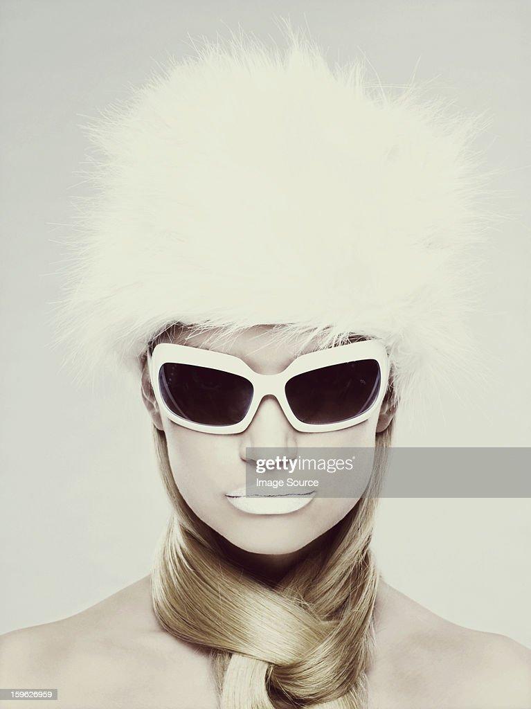 Jeune femme portant des lunettes de soleil et Chapeau de fourrure blanche