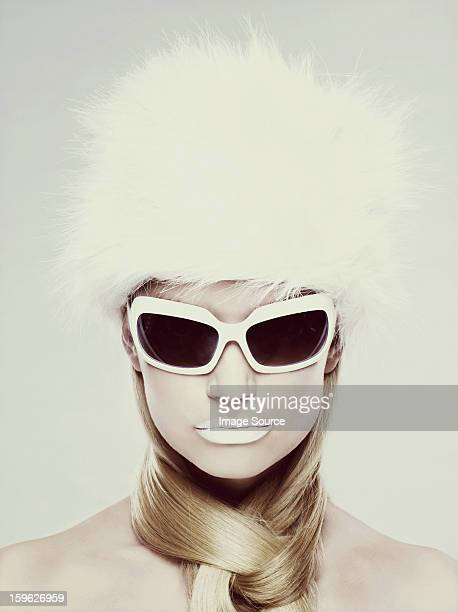 Young woman wearing white sunglasses and fur hat