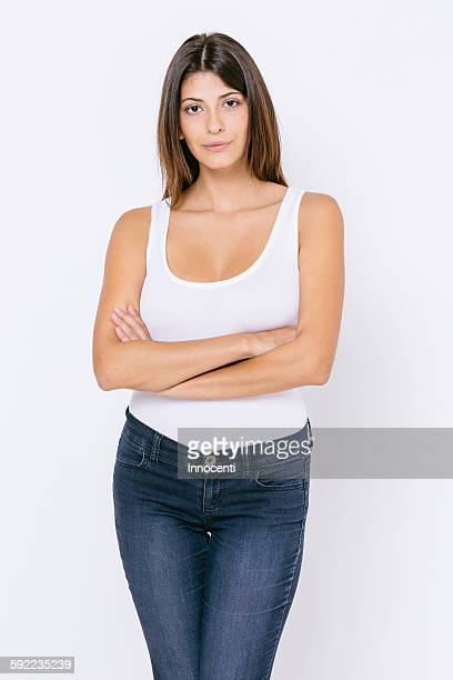Young woman wearing white vest and skinny jeans arms crossed looking at camera
