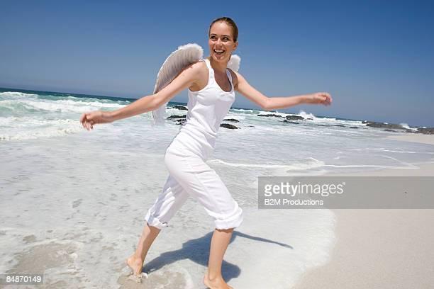 Young woman wearing wings walking on beach