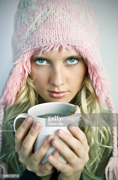 Young Woman Wearing Winter Hat Holding Cup of Tea