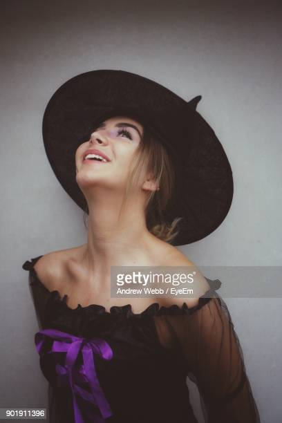Young Woman Wearing Witch Hat Against Gray Background