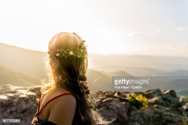 Young Woman Wearing Wreath Against Sky