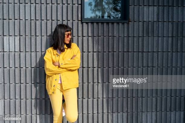 young woman wearing yellow jeans clothes, looking away - schwarzes haar stock-fotos und bilder