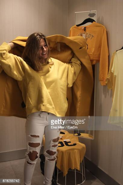 Young Woman Wearing Yellow Overcoat In Room