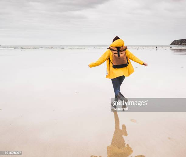 young woman wearing yellow rain jacket and running at the beach, bretagne, france - yellow shoe stock pictures, royalty-free photos & images