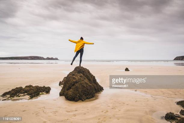 young woman wearing yellow rain jacket at the beach, bretagne, france - yellow coat stock pictures, royalty-free photos & images
