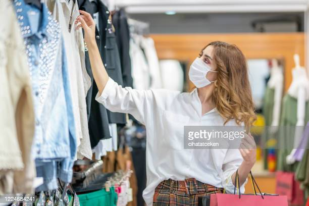 a young woman wears a protective mask while shopping at the mall. - merchandise stock pictures, royalty-free photos & images