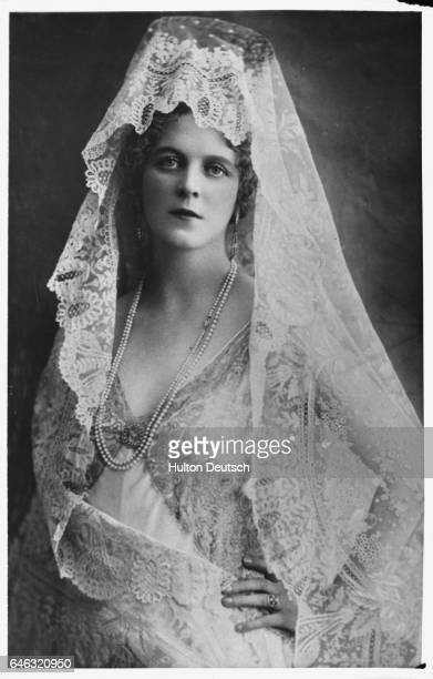 A young woman wears a white lace mantilla and pearls