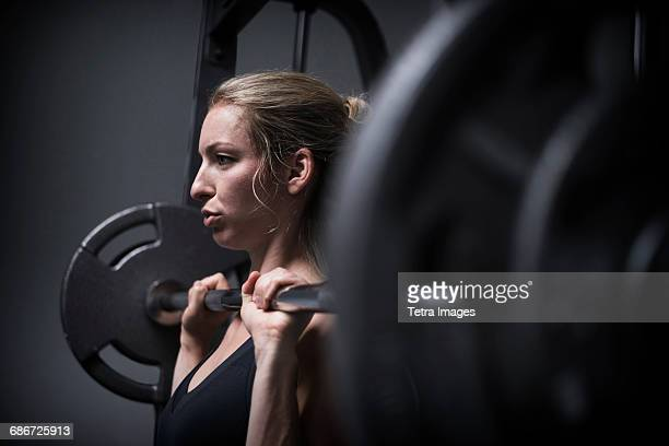 young woman weightlifting in gym - weight training stock pictures, royalty-free photos & images