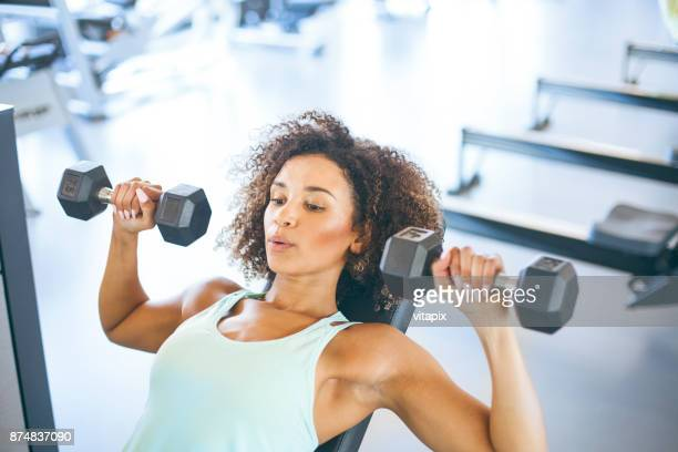young woman weightraining at the gym - sollevare foto e immagini stock