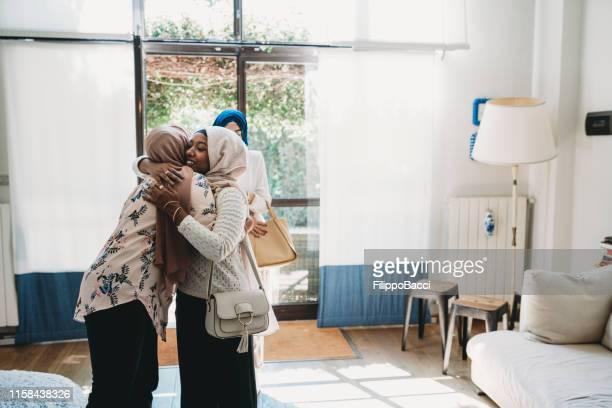 jeune femme accueillant ses amis à la maison - islam photos et images de collection