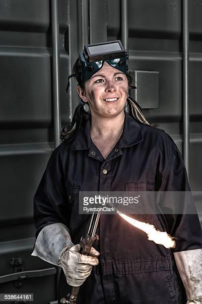 junge frau schweißer mit fackel flame, industrielle ambiente. - schutzbrille stock-fotos und bilder