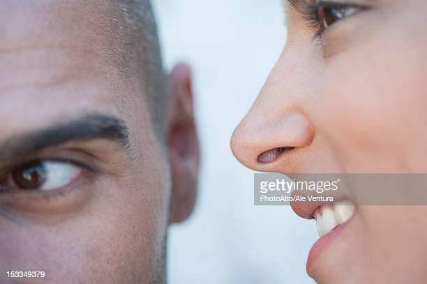 Young woman whispering in man's ears, cropped