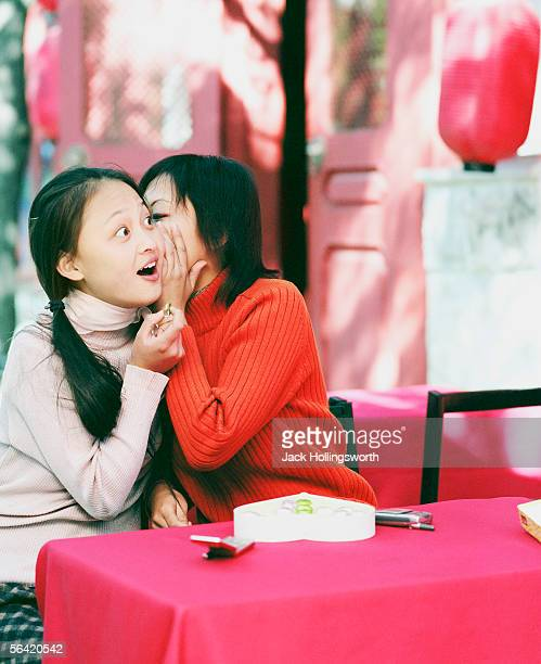 Young woman whispering into another woman's ear