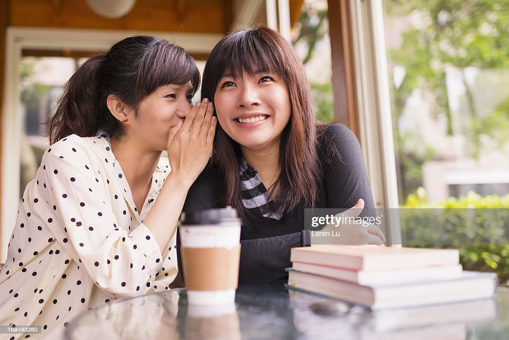 Young woman whispering into other womans ear : Stock Photo