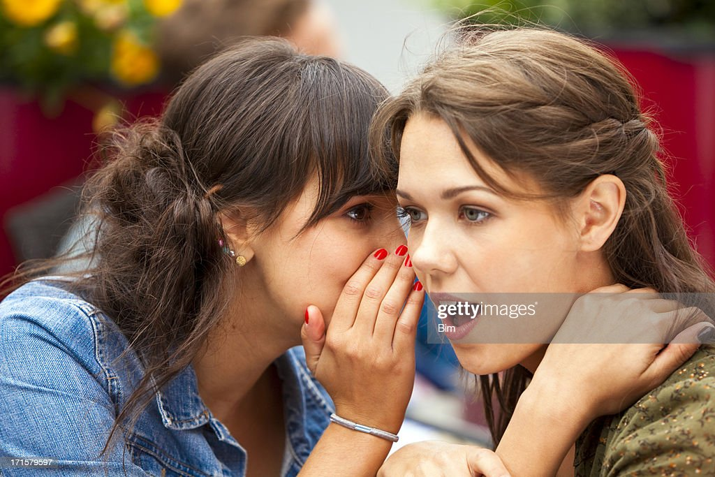 Young Woman Whispering Secret in Another Woman's Ear at Cafe : Stock Photo