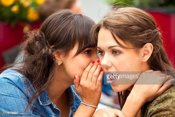 Junge Frau Flüstern Geheimnis in eine andere Frau hören im Café