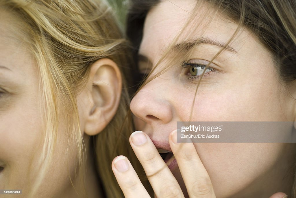 Young woman whispering secret into friend's ear, close-up : Stock Photo