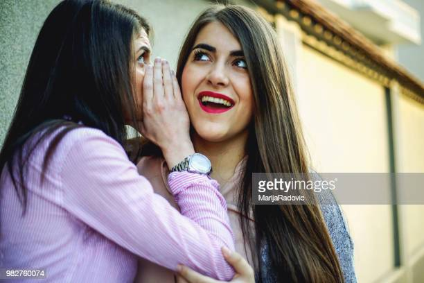 Young woman whispering to her best friend gossips or funny secrets