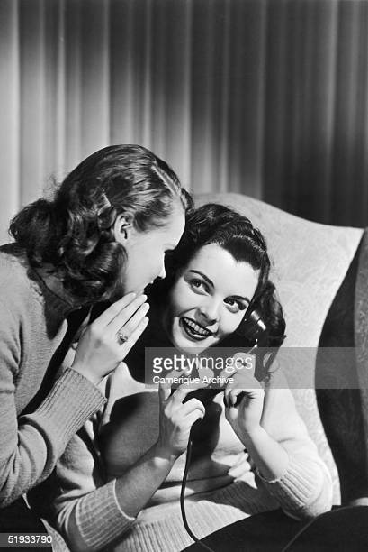 A young woman whispers something to her friend who is making a telephone call circa 1945