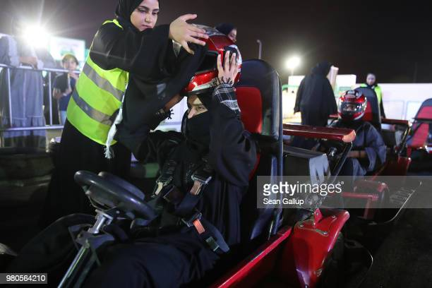 A young woman who is wearing a traditional Muslim niqab gets help puting on a helmet as she prepares to drive a gokart at an outdoor educational...
