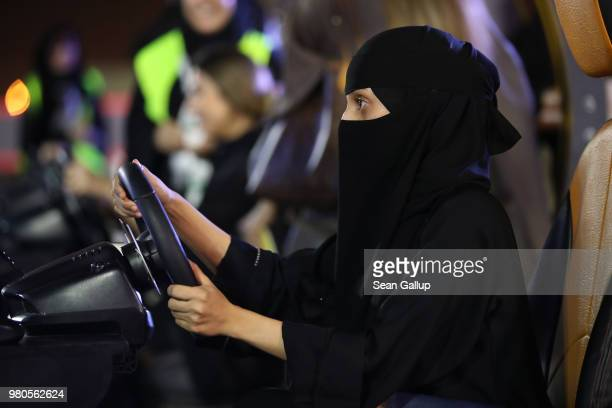 A young woman who is wearing a traditional Muslim niqab tries out a car driving simulator during an outdoor educational driving event for women on...