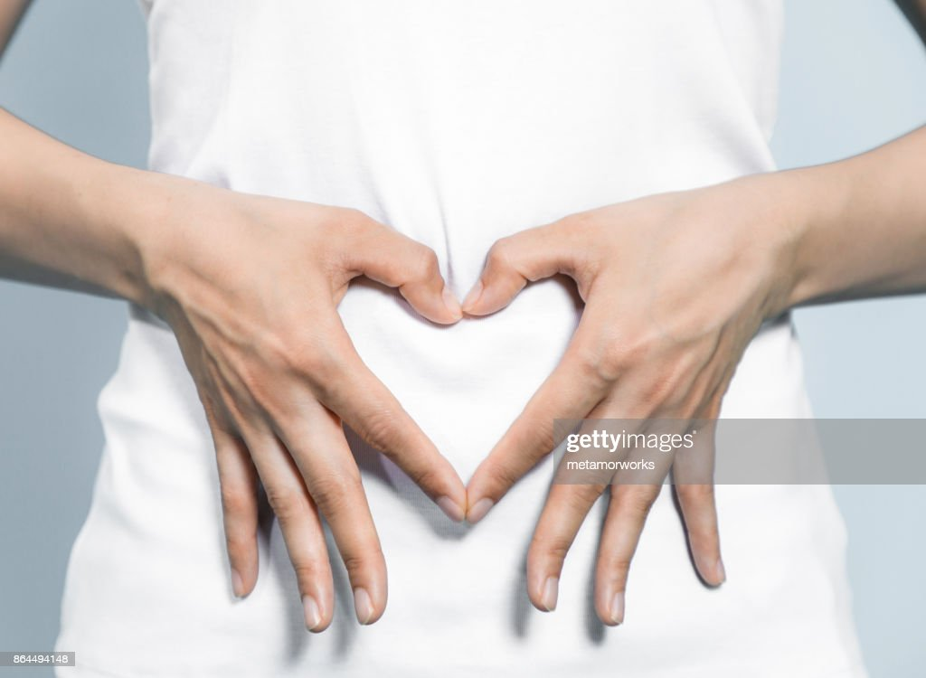 young woman who makes a heart shape by hands on her stomach. : Stock Photo