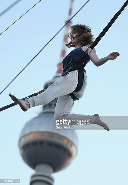 Young woman, who was visiting from Stuttgart and was in Berlin for the first time in her life, jumps on a trampoline in a bungee harness at Alexander...