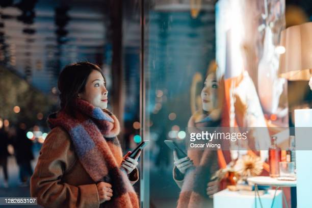 young woman window shopping in the city at night - buying stock pictures, royalty-free photos & images