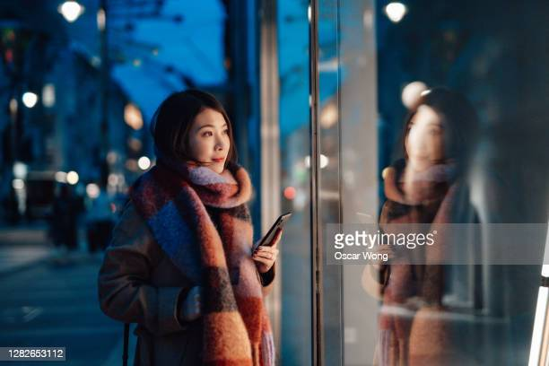 young woman window shopping in the city at night - ショーウィンドウ ストックフォトと画像