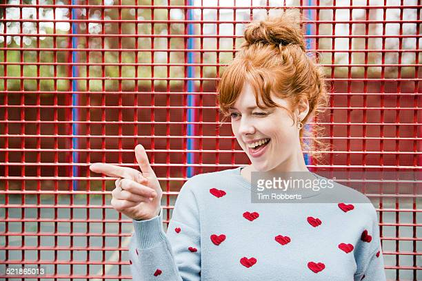 young woman winking and pointing. - gesturing stock pictures, royalty-free photos & images