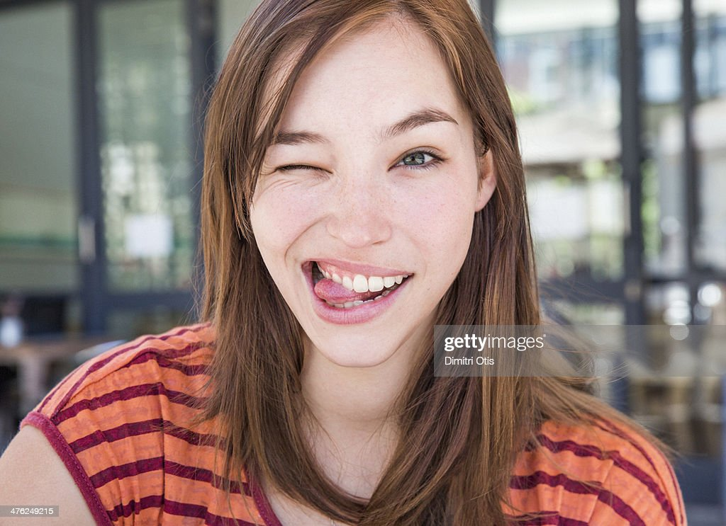 Young woman winking with her tongue out : Stock Photo