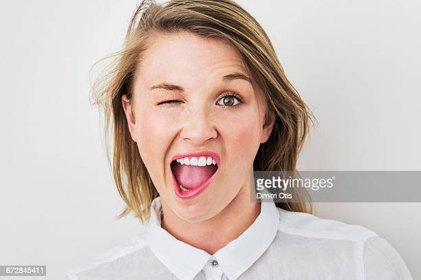 Young woman winking with mouth wide open