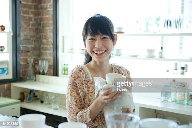 Young woman wiping coffe cup with towel in kitchen
