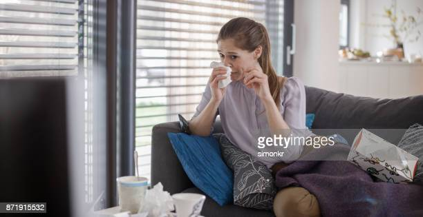 Young woman wiping her nose while watching sad movie