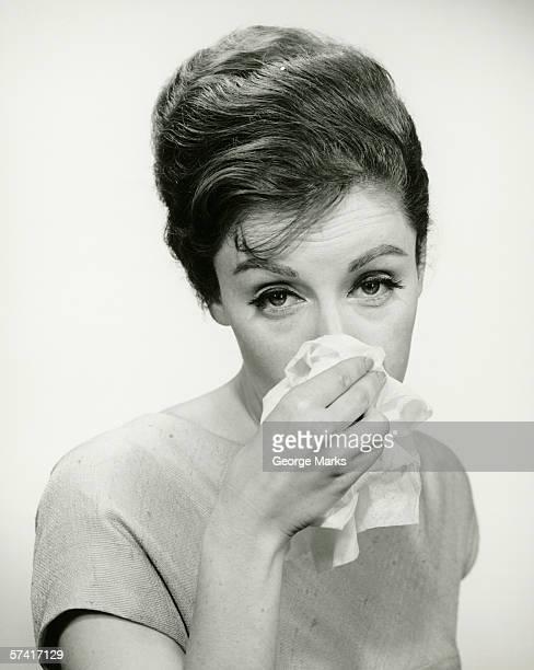 jeune femme s'essuyer le nez avec mouchoir, posant en studio. - handkerchief photos et images de collection
