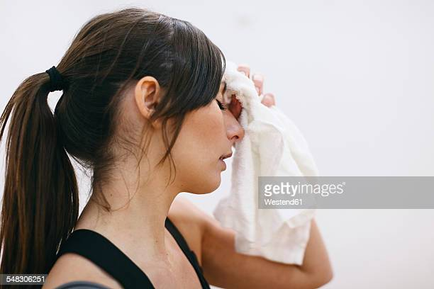 young woman wiping off sweat from her forehead - rubbing stock pictures, royalty-free photos & images
