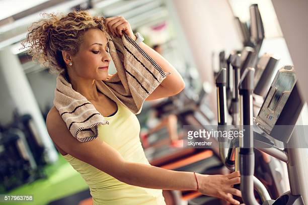 Young woman wiping sweat with a towel in a gym.