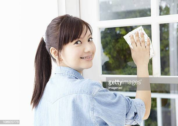 young woman wiping the window - 後ろで束ねた髪 ストックフォトと画像