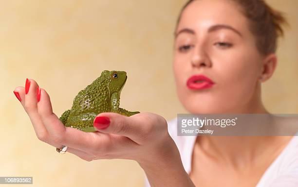 Young woman wishing kissing frog