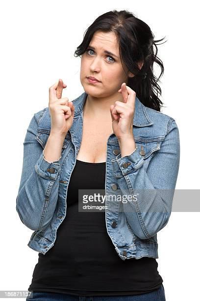 Junge Frau, die mit gekreuzten Fingern