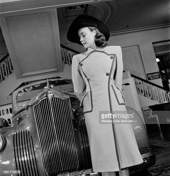 Young woman with a 1941 Packard 120 at a car showroom, USA, 1941.