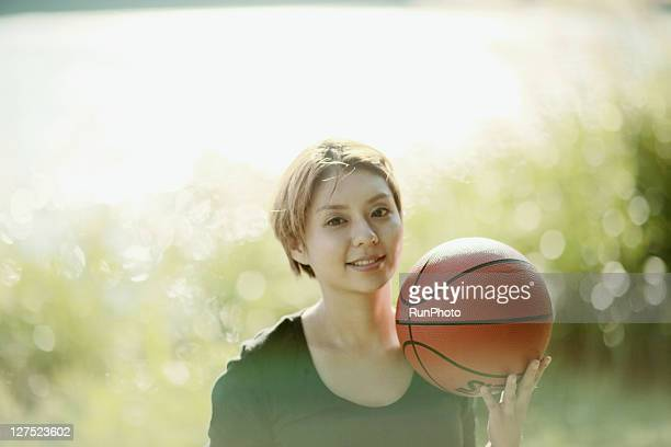 young woman with a basket ball near the lake