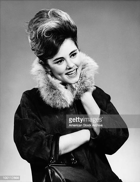 A young woman with a beehive hairstyle and a coat with a fur collar circa 1967