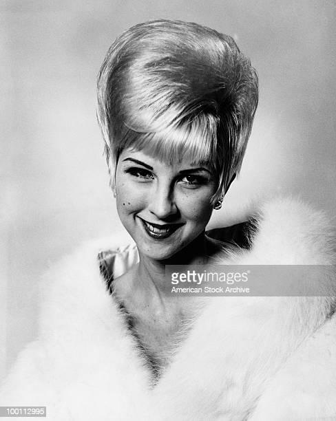 A young woman with a beehive hairstyle and wearing a fur coat circa 1963
