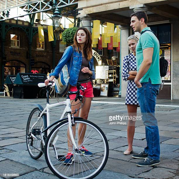 CONTENT] A young woman with a bicycle and a couple watch street entertainment on a summer evening in the Piazza Covent Garden London