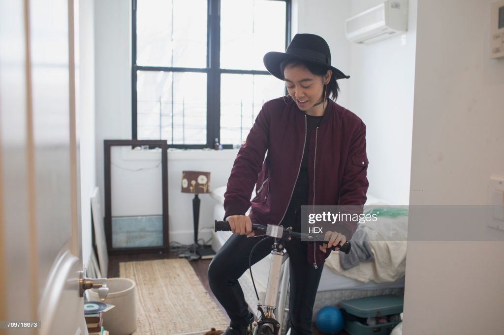 A young woman with a bicycle in a bedroom : Foto de stock