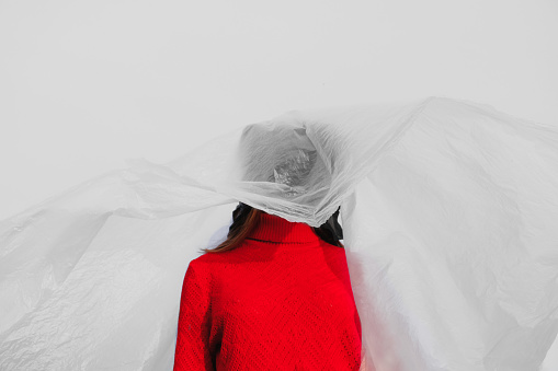 Young woman with a black plastic bag on her head dressed in a red jumper on a plastic background - gettyimageskorea
